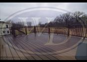 Elgin, IL - Decking: Trex Transcend Spiced Rum - Railing, Posts, Fascia, & Boarder: Trex Transcend Vintage Lantern - Balusters: Trex Bronze Square Aluminum - Lighting: Bronze Riser Lights, Vintage Lantern Cap Lights, & Six Can Lights - Other: Trex Elevations & Rain Escapes